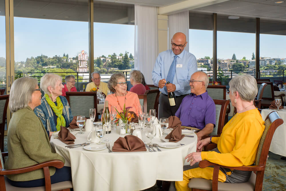 5 people at table with wine being opened