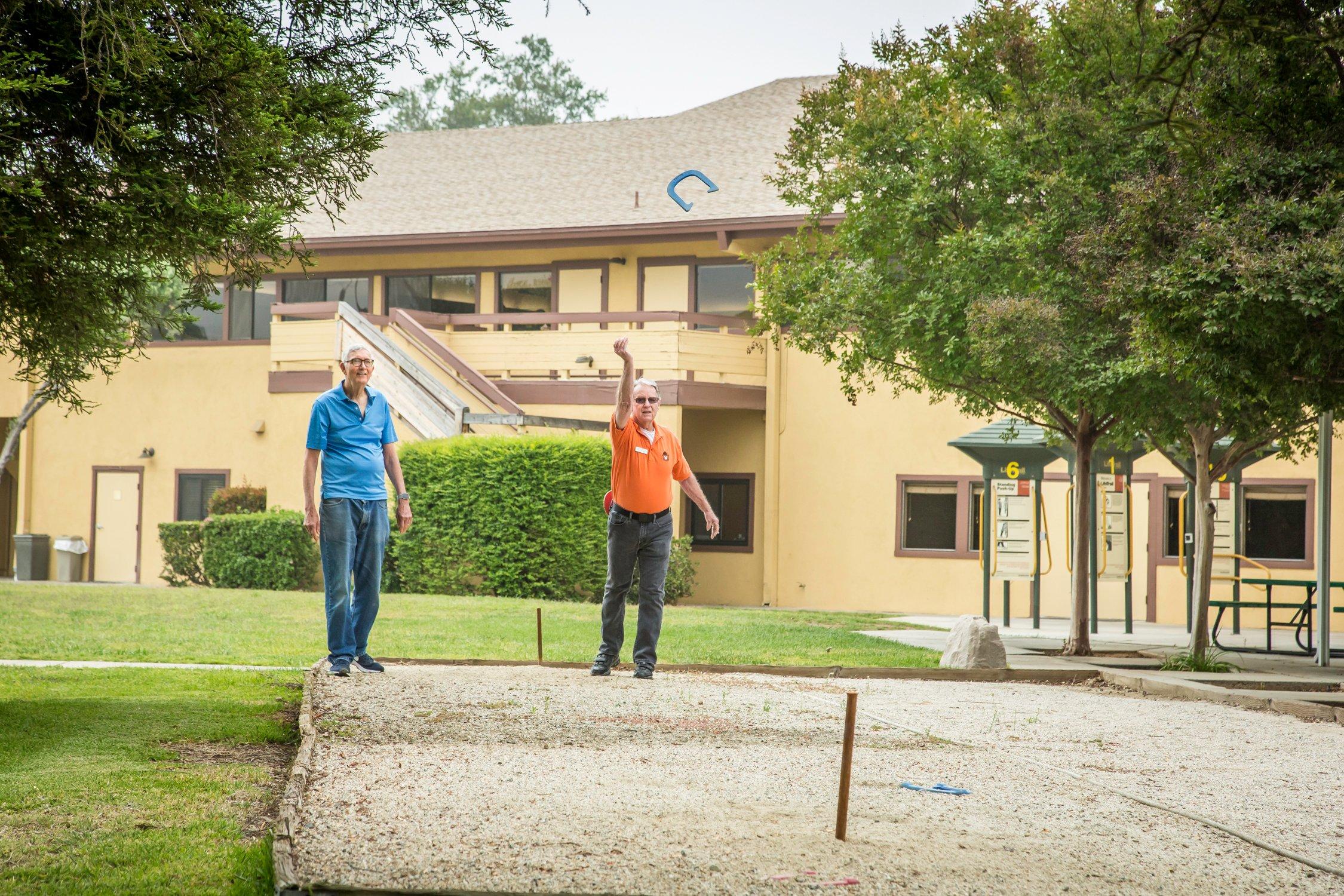 2 men throwing horseshoes