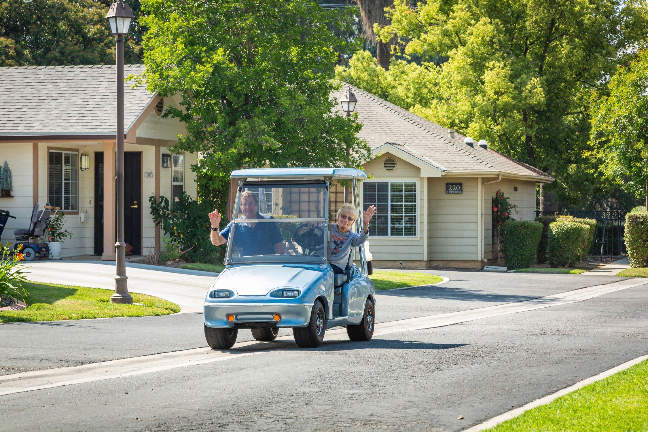 golf cart couple waving