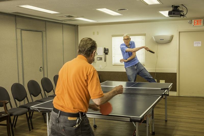 two residents play ping pong together