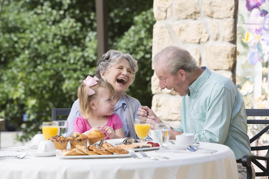 Grandparents eating breakfast with grandchild