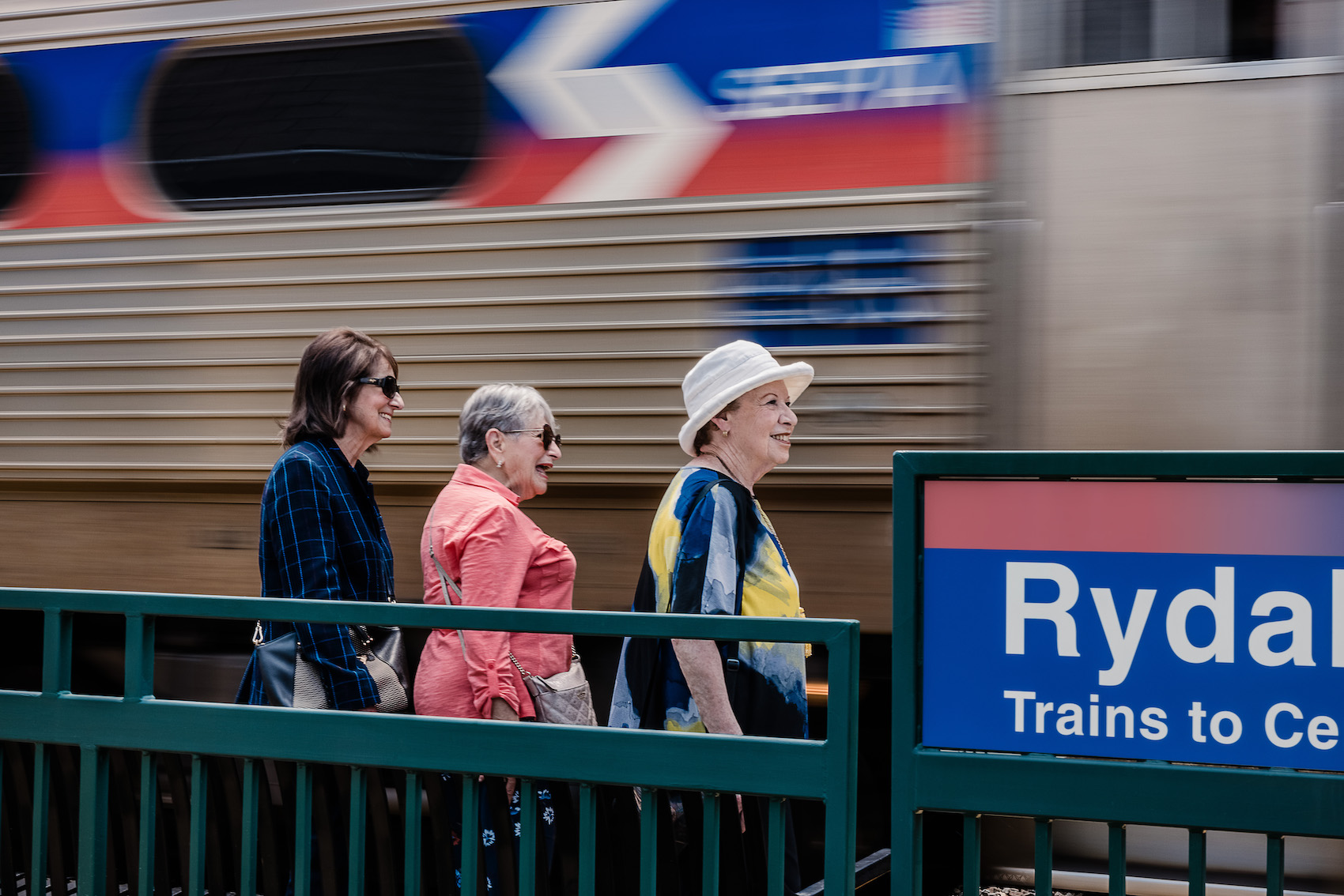 three women getting on a train