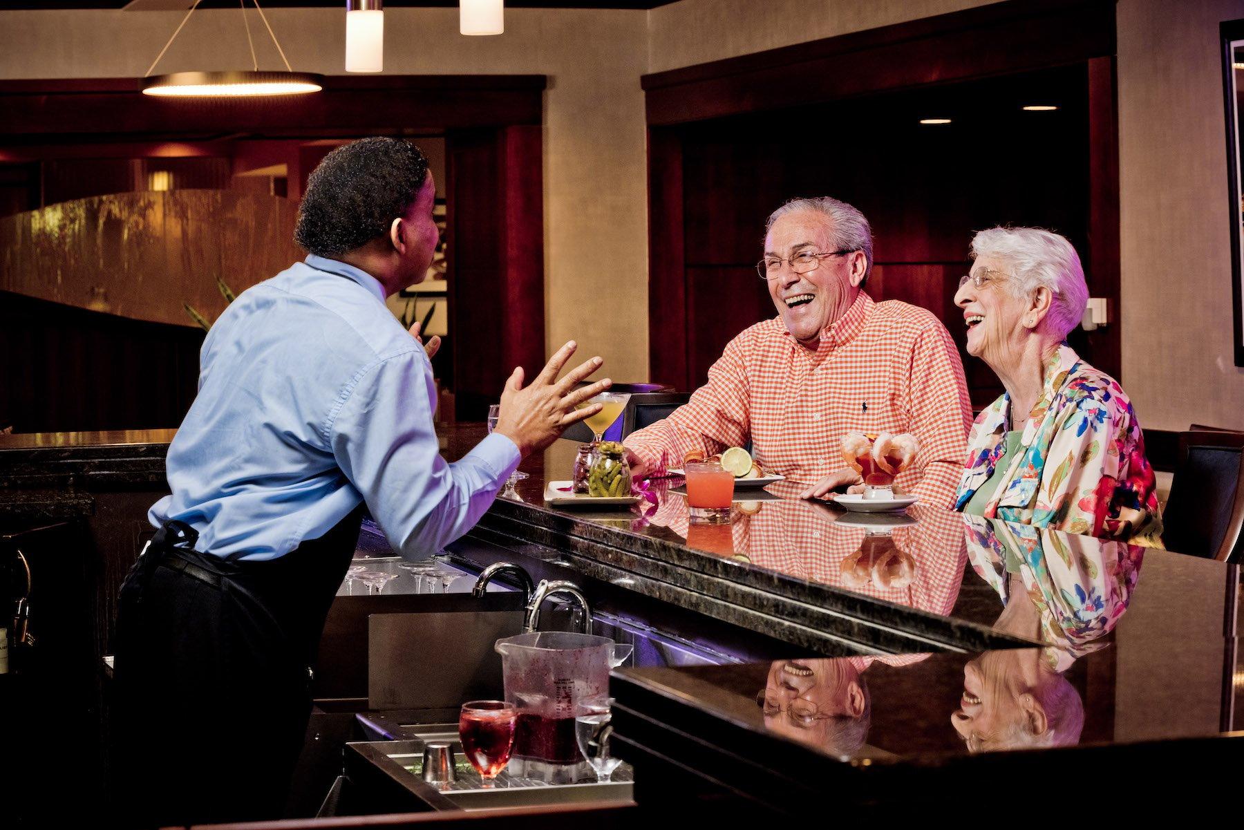 older couple at bar with bartender