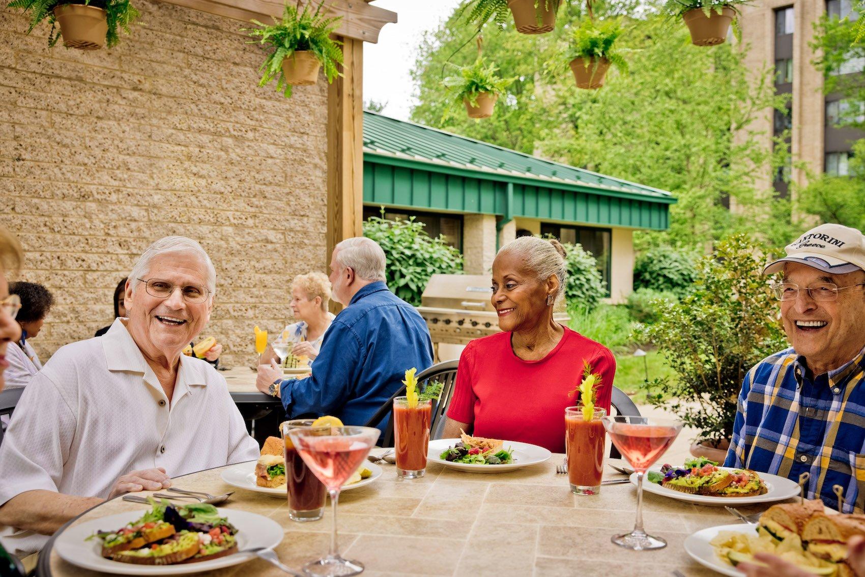 three people eating a senior living community