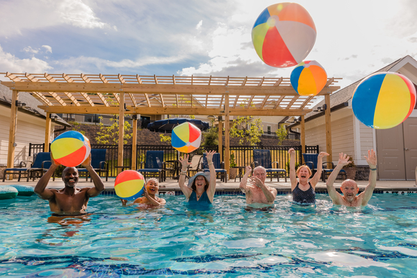 people playing with beach balls in pool