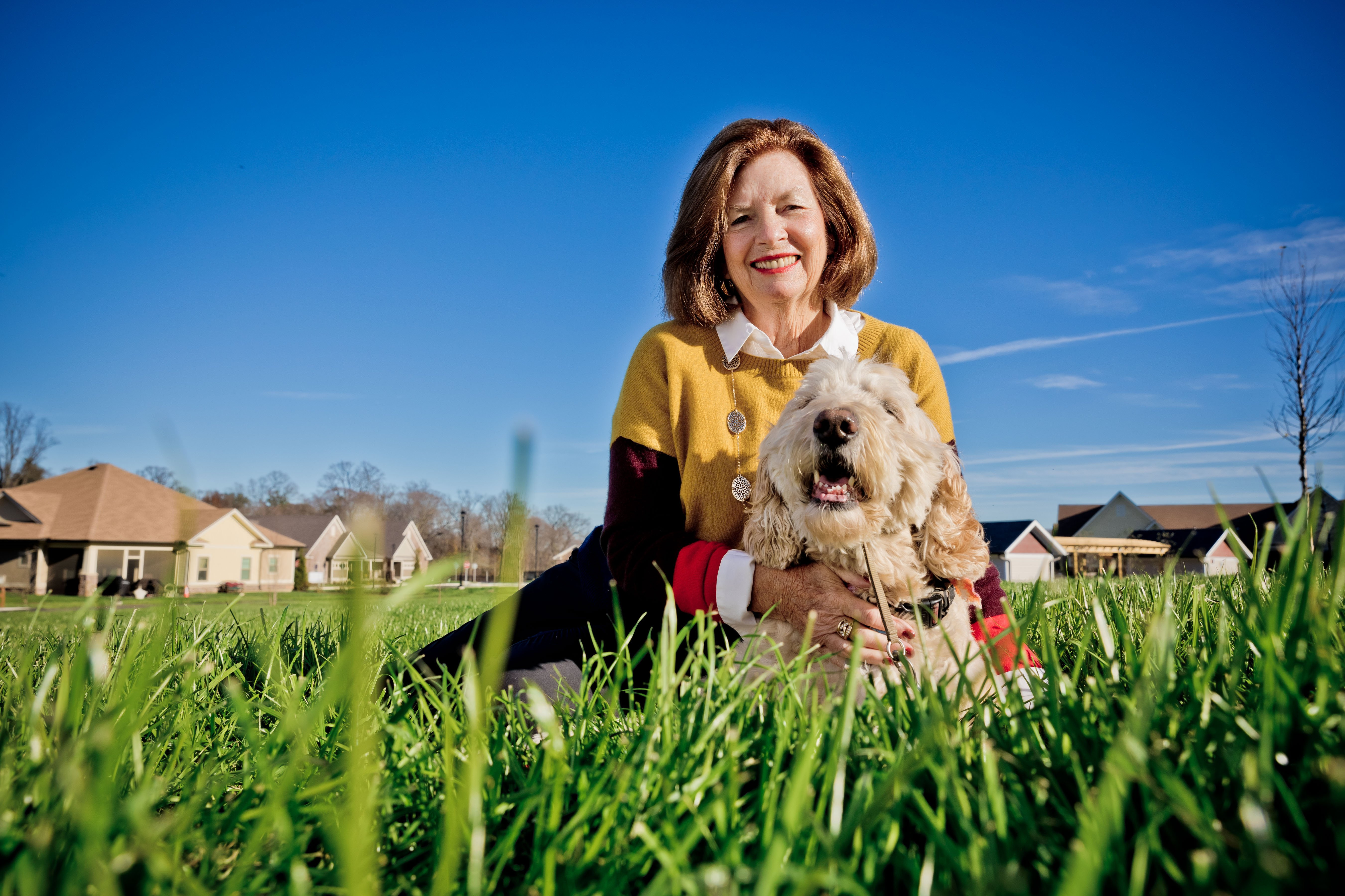woman and dog sitting in grass
