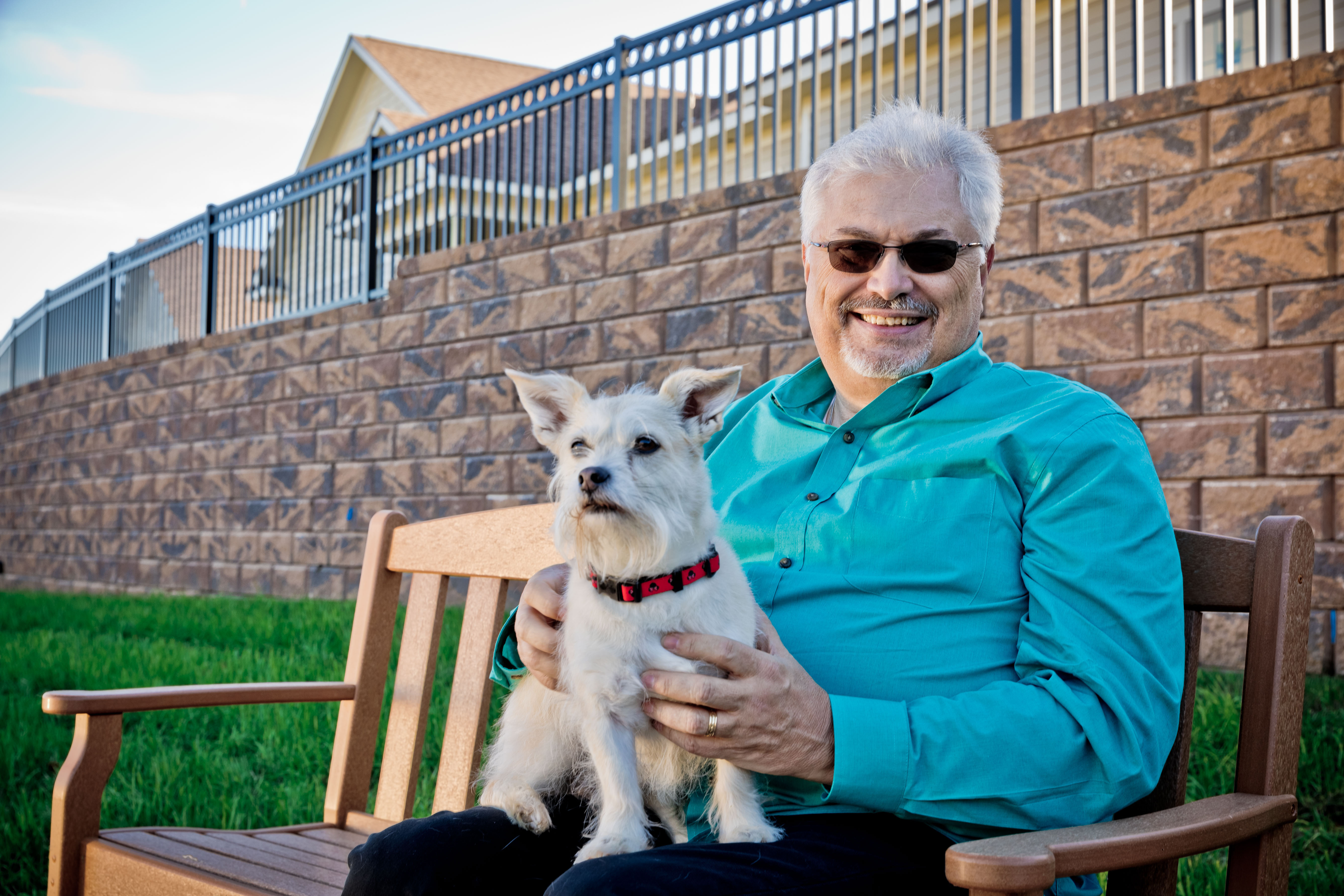 man sitting on bench with dog in his lap