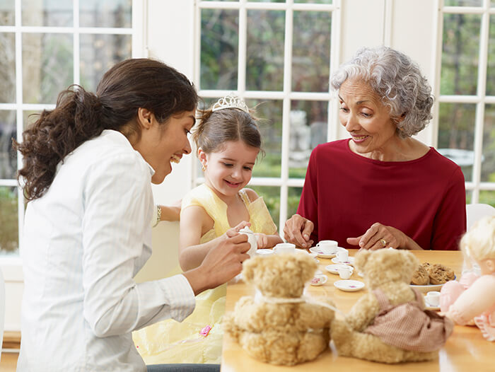 Mother and grandmother share a tea party with young girl.
