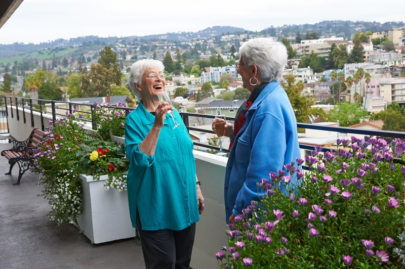2 female residents enjoy the patio with wine