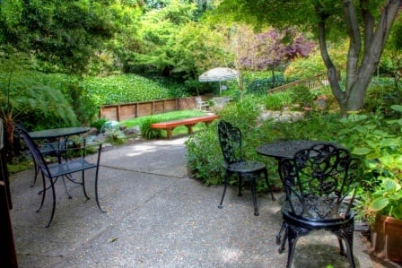 lush part of garden with black metal tables/chairs