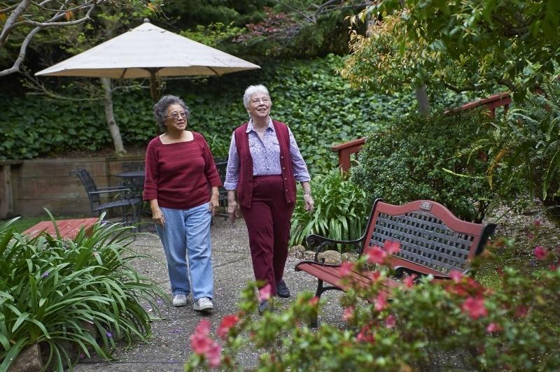 2 women walking in garden