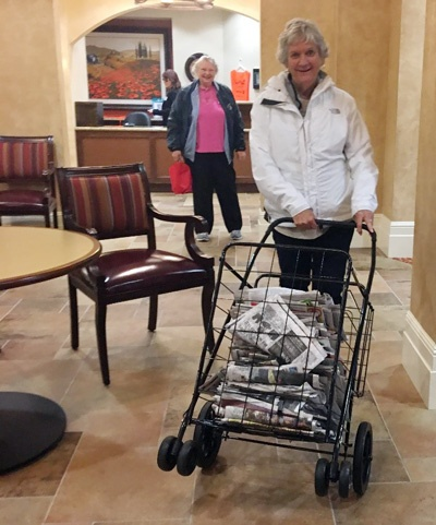 Beverly Johnson follows Patsy Agee, a resident at The Terraces, pushing a cart full of newspapers to donate.