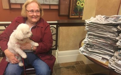 Pat Parnell, a resident at The Terraces of San Joaquin Gardens, sits with her dog Coco Chanel next to a stack of donated newspapers.
