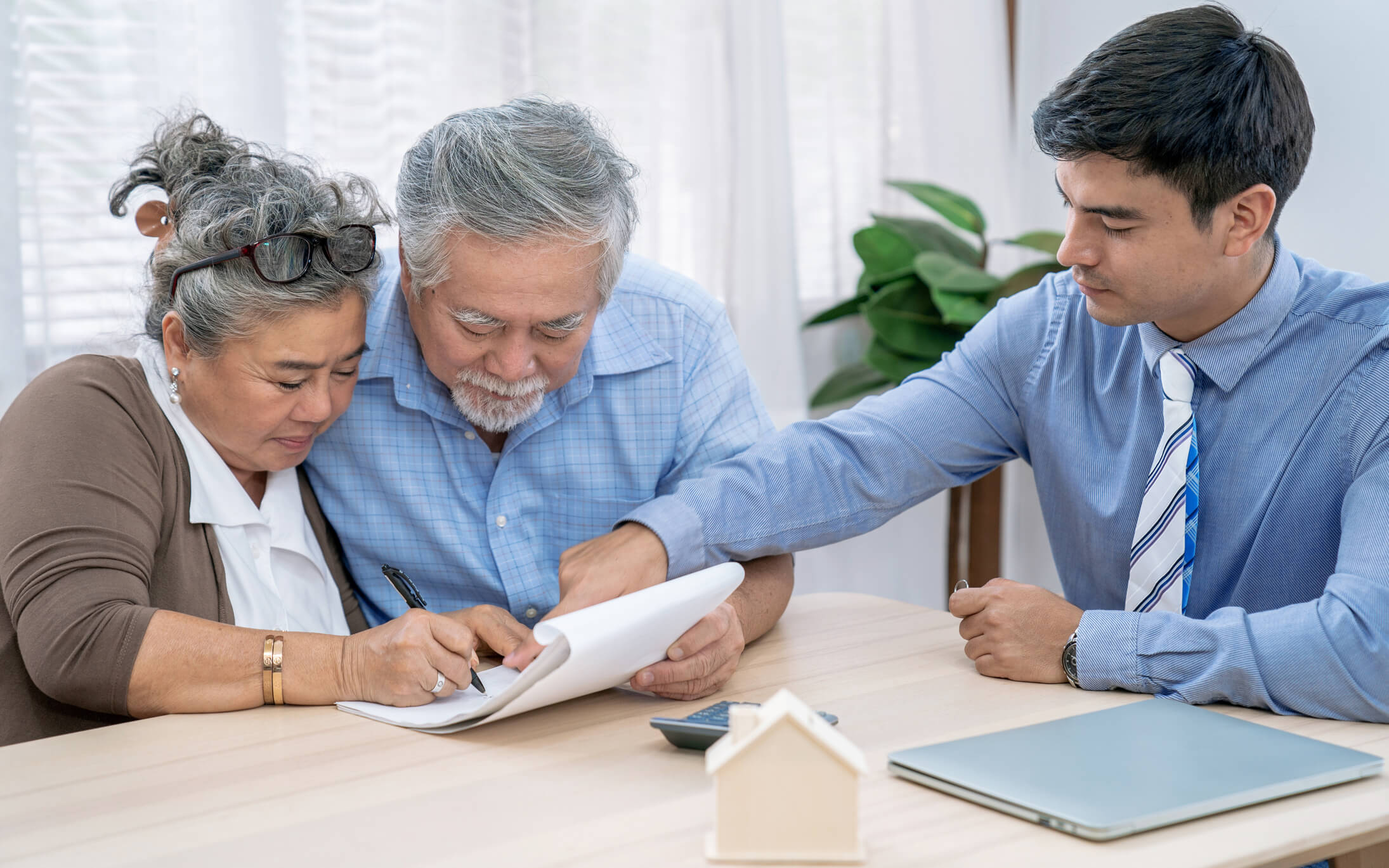 Couple reviewing paperwork with real estate agent.