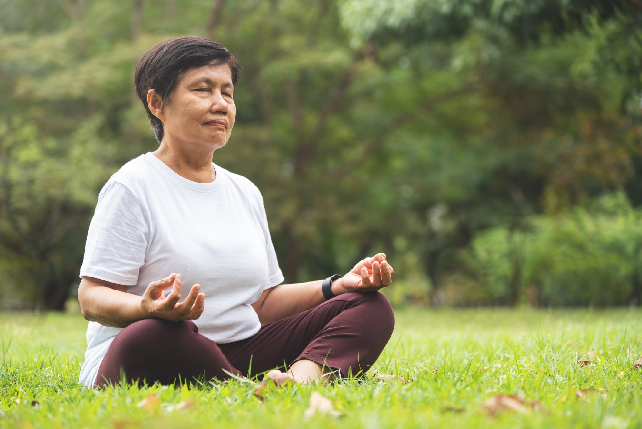 Older woman meditating outside
