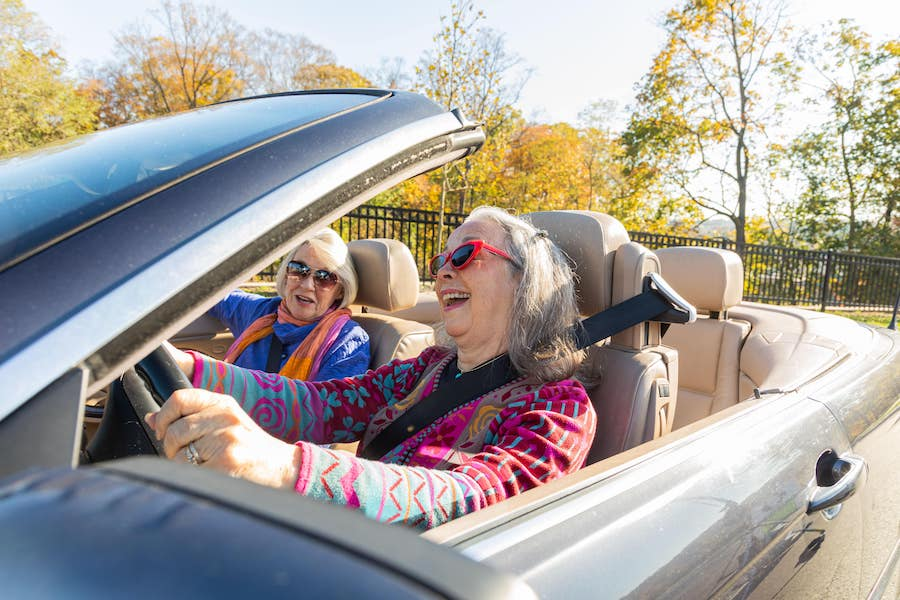Two happy senior women driving a convertible