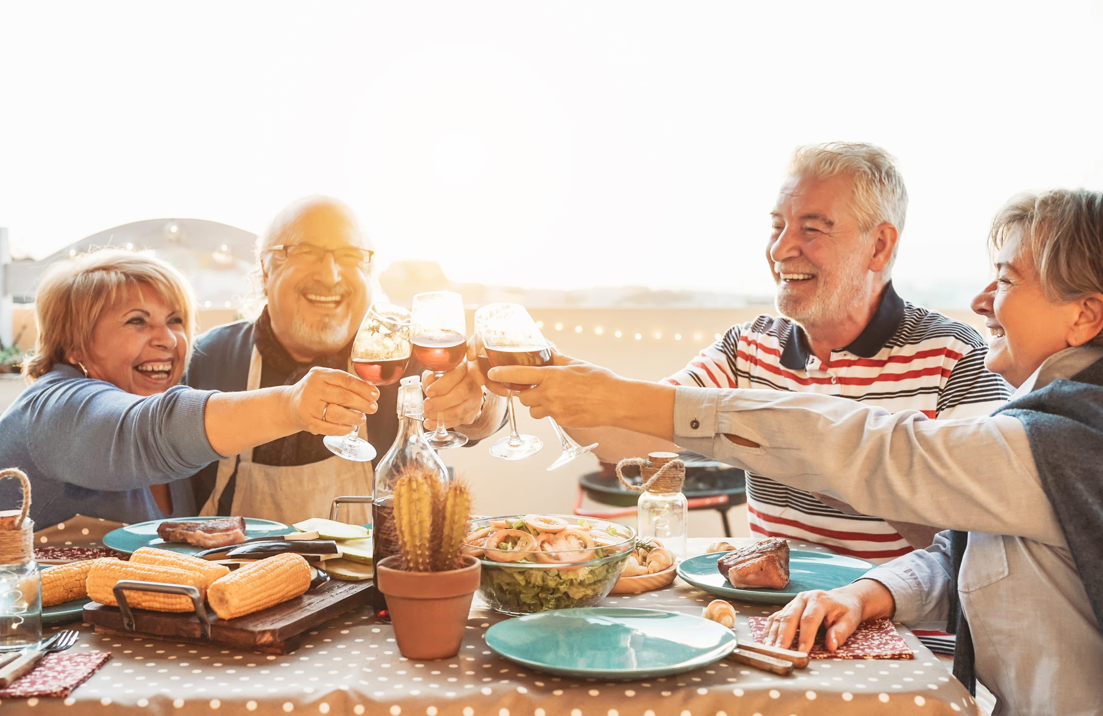Seniors toasting, eating outside together