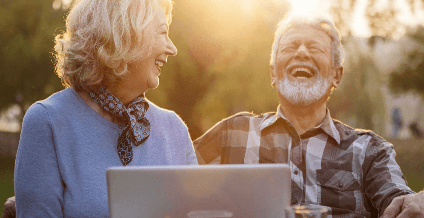 Older couple laughing in front of a laptop